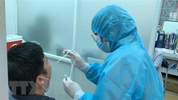 Nhân viên Trung tâm Y tế Quận 3 lấy mẫu xét nghiệm cho người dân. (Ảnh: Đinh Hằng/TTXVN)