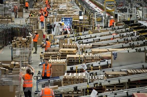Nhân viên đóng gói hàng hóa cho khách hàng tại một trung tâm dịch vụ của Amazon. (Ảnh: AFP/TTXVN)