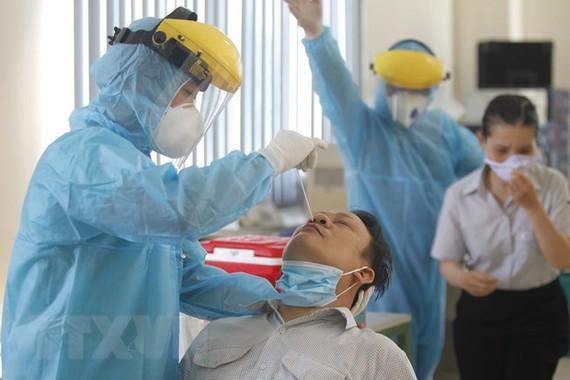 Các y bác sỹ Trung tâm y tế Quận 7 thực hiện xét nghiệm sàng lọc COVID-19 ngẫu nhiên cho công nhân tại Công ty TNHH Kim may Organ Việt Nam. (Ảnh: Thanh Vũ/TTXVN)