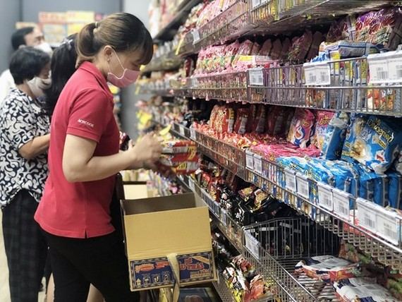 Nhân viên nhãn hàng bổ sung thêm hàng hóa thiết yếu lên kệ tại siêu thị ở TP Hồ Chí Minh. (Ảnh: Mỹ Phương - TTXVN.)