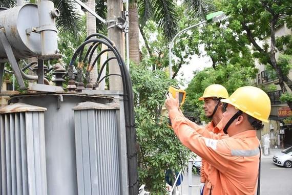 Nhân viên EVNHANOI kiểm tra tình trạng vận hành của thiết bị điện. (Ảnh: PV/Vietnam+)