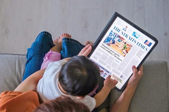 Người dân Singapore xem báo The Straits Times trên máy tính bảng.