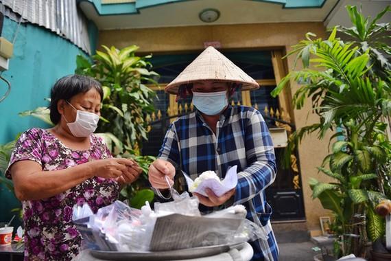 Cô Nguyễn Thị Oanh (Q.4, TP.HCM) cho biết cô bán xôi bắp cũng đã được 20 năm, nuôi 2 con ăn học. Trước khi dịch cô nấu cả nồi, giờ dịch cô giảm số lượng còn phân nửa mà bán rất chậm - Ảnh: NGỌC PHƯỢNG