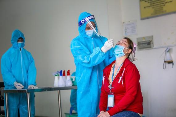 Cán bộ y tế test nhanh Covid-19 cho công nhân trên địa bàn Hậu Giang.