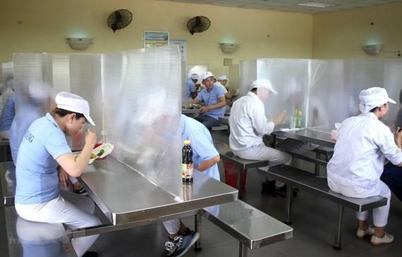 Nhà ăn của công nhân có vách ngăn, đảm bảo giãn cách. (Nguồn: TTXVN)