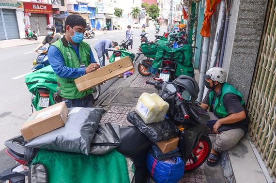 Shipper lấy hàng trên đường Nguyễn Kiệm, quận Phú Nhuận (TP.HCM) để giao cho khách vào sáng 20-9 - Ảnh: QUANG ĐỊNH