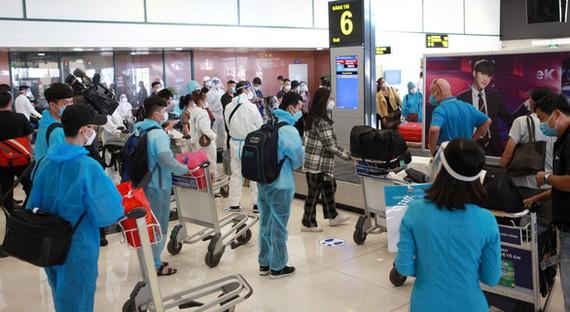 Tất cả hành khách từ TP.HCM ra Hà Nội đều phải tiêm đủ 2 mũi vắc xin, xét nghiệm âm tính với SARS-CoV-2 nhưng nhiều người vẫn mặc đồ phòng dịch rất cẩn thận - Ảnh: TUẤN PHÙNG
