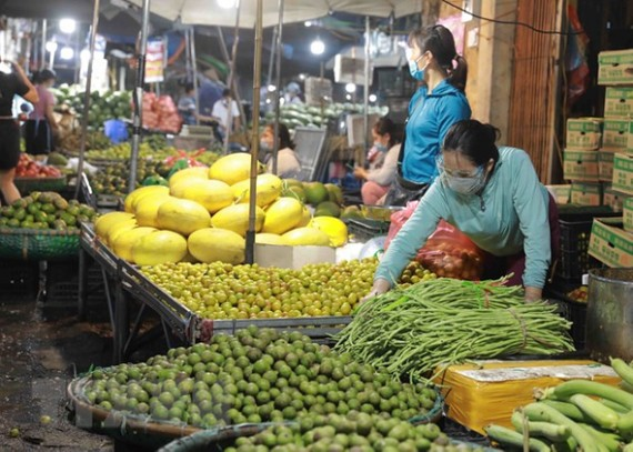 Tiểu thương chuẩn bị hàng rau, quả tại chợ đầu mối Nam Hà Nội. (Ảnh: Vũ Sinh/TTXVN)