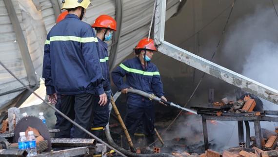Lực lượng chức năng phun nước dập những khu vực có khả năng bộc phát lửa lại sau cơn cháy