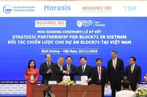 Phó Thủ tướng Vương Đình Huệ (hàng sau, thứ 3 từ trái sang) cùng lãnh đạo tỉnh Bình Dương chứng kiến lễ ký kết giữa Becamex IDC và các đối tác