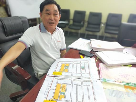 Ông Huỳnh Uy Dũng bên sơ đồ vị trí 255 lô đất nền muốn tặng