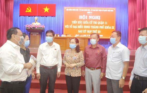Chủ tịch HĐND TPHCM Nguyễn Thị Lệ trao đổi với các đại biểu dự hội nghị tiếp xúc cử tri quận 11. Ảnh: CAO THĂNG