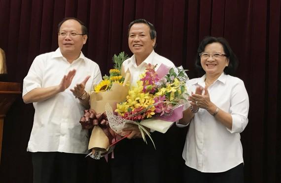 Đồng chí Tất Thành Cang và đồng chí Thân Thị Thư, Ủy viên Ban Thường vụ Thành ủy TPHCM, trao quyết nghỉ hưu và tặng hoa cho đồng chí Huỳnh Văn Chúm (giữa). Ảnh: KIỀU PHONG