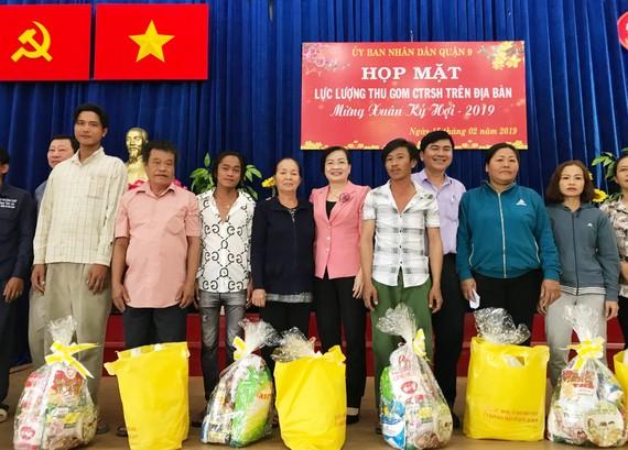 Lãnh đạo quận 9 tặng quà cho những người thu gom rác dân lập ở quận có điều kiện khó khăn. Ảnh: KIỀU PHONG