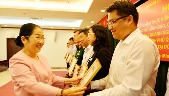 Phó Bí thư Thành ủy Võ Thị Dung tặng bằng khen cho các cá nhân tại hội nghị tổng kết 10 năm thực hiện Chỉ thị 22-CT/TW của Ban Bí thư. Ảnh: VIỆT DŨNG