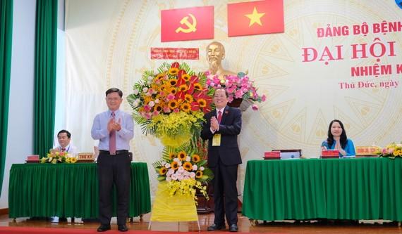 Bí thư Quận ủy Thủ Đức Nguyễn Mạnh Cường (trái) tặng hoa chúc mừng Đại hội Đảng bộ Bệnh viện quận Thủ Đức. Ảnh: KIỀU PHONG