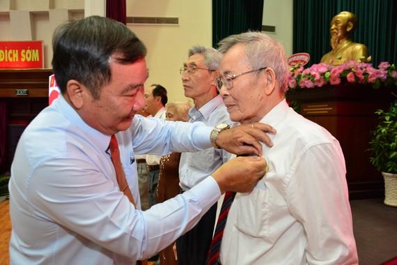 Bí thư Quận ủy quận 2 Trần Văn Thuận (trái) trao Huy hiệu Đảng cho các đảng viên cao tuổi Đảng trên địa bàn quận. Ảnh: KIỀU PHONG