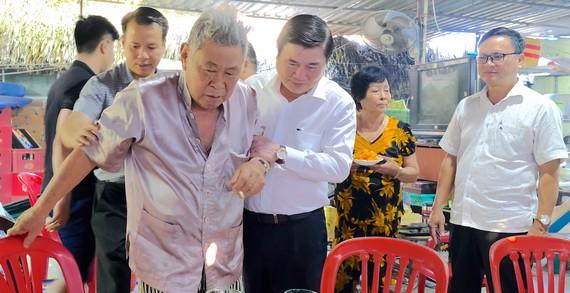 Chủ tịch UBND TPHCM ân cần thăm hỏi sức khỏe ông Huỳnh Quang Hải và  gia đình ông. Ảnh: KIỀU PHONG