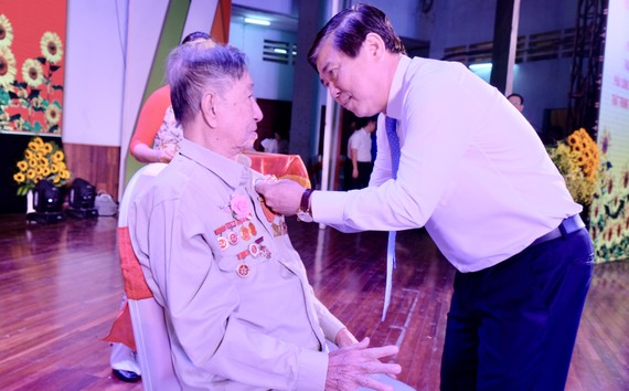 Đồng chí Nguyễn Thành Phong trao Huy hiệu 70 năm tuổi Đảng cho Đảng viên Quận Thủ Đức. Ảnh: KIỀU PHONG