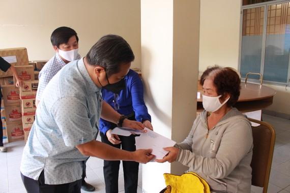 Phó Bí thư Thường trực Huyện ủy Hóc Môn Nguyễn Anh Tuấn trao tiền hỗ trợ cho người bán vé số lưu động. Ảnh: QUỲNH THY