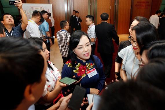 Bộ trưởng Bộ Y tế Nguyễn Thị Kim Tiến trao đổi với phóng viên bên hành lang kỳ họp sáng nay, 21-10