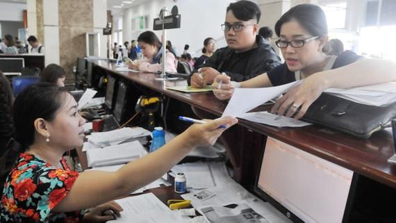 Đại diện doanh nghiệp trao đổi với nhân viên Cục thuế TPHCM. Ảnh: CAO  THĂNG