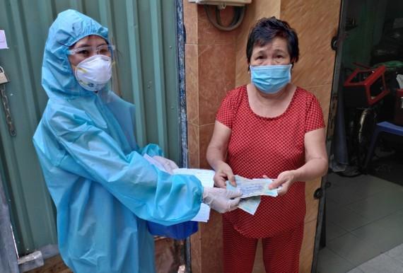 Công chức phường mặc đồ bảo hộ y tế vào tận các khu phong tỏa trao tiền hỗ trợ cho người dân