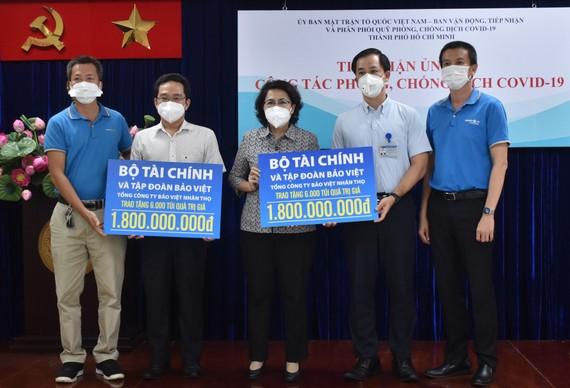 Chủ tịch Ủy ban MTTQ Việt Nam TPHCM Tô Thị Bích Châu tiếp nhận bảng tượng trưng ủng hộ từ đại diện Bộ Tài chính và Tập đoàn Bảo Việt