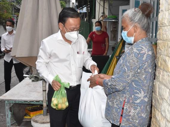 Trưởng Ban Dân vận Thành ủy TPHCM Nguyễn Hữu Hiệp tặng quà một số hộ dân đồng bào dân tộc có hoàn cảnh khó khăn ở quận Tân Bình. Ảnh: ĐÌNH LÝ