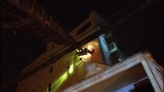 Lực lượng dùng xe thang tiếp cận đưa 24 người mắc kẹt trong vụ cháy chung cư mini ra ngoài an toàn. Ảnh: C.T