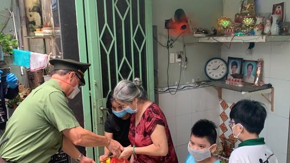 Thiếu tướng Cao Đăng Hưng trao quà tận tay người dân có hoàn cảnh khó khăn ở phường 8, quận 4, TPHCM. Ảnh: CHÍ THẠCH