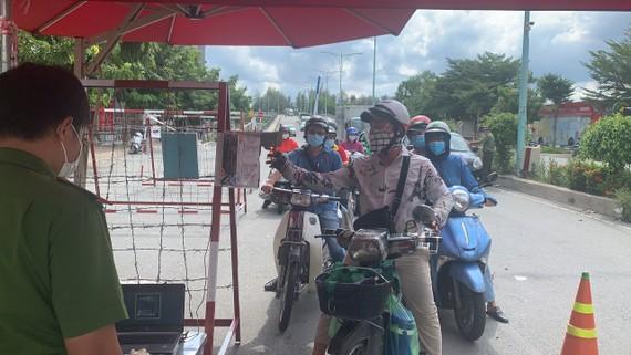 Kiểm tra người dân lưu thông qua chốt kiểm soát chân cầu Him Lam, quận 7 vào chiều ngày 15-9. Ảnh: CHÍ THẠCH