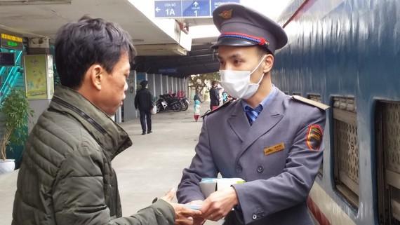 Nhân viên đường sắt phát khẩu trang cho hành khách đi tàu