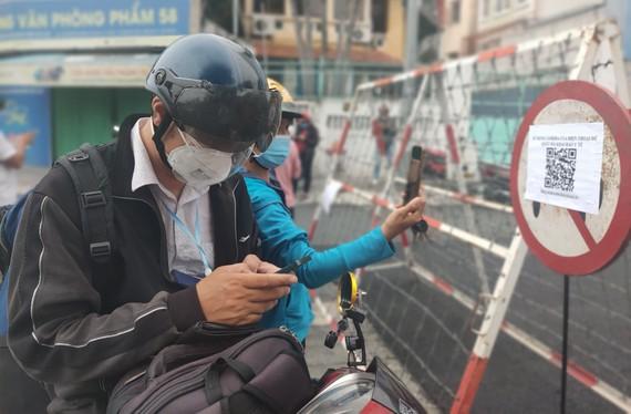 Người dân khai báo tại trạm kiểm soát trên đường Nguyễn Bỉnh Khiêm. Ảnh: DŨNG PHƯƠNG