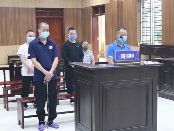 4 bị cáo (đứng) tại tòa. Ảnh: L.N.