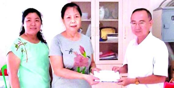 本報編委兼編輯部主任范興(右一)向林秀蓉移交4000萬元修繕房屋經費。