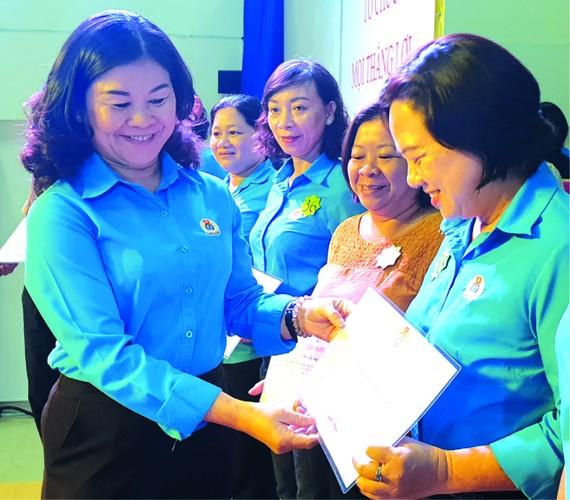 第五郡勞動聯團主席黎氏碧幸向女職工頒發模範獎。