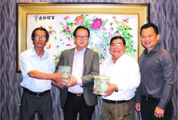 萬盛發集團代表張豐裕(左二)向二府會館 和建築單位代表移交第三期捐款。