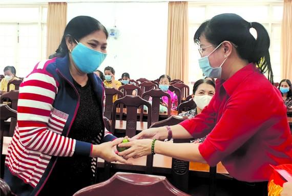 郡婦聯會主席陳氏雪幸(右)向各民族 婦女派發紅包。