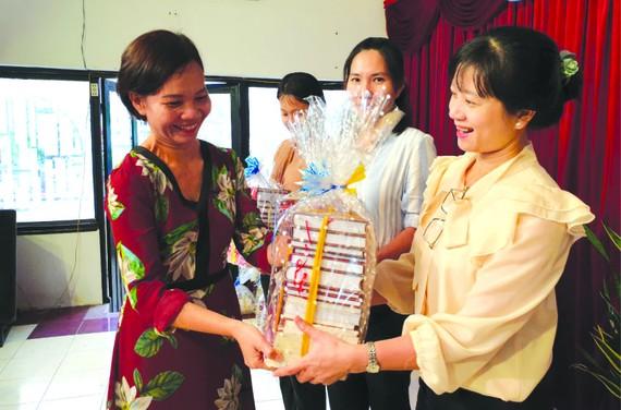 市綜合科學圖書館傳媒部門主任阮氏如莊(左一)向各校贈送書籍。