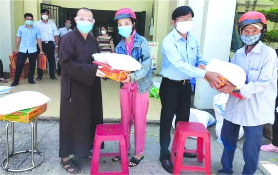 釋玄雄法師與平新郡平治東A坊人委會主席何英俊向貧困者贈送禮物。
