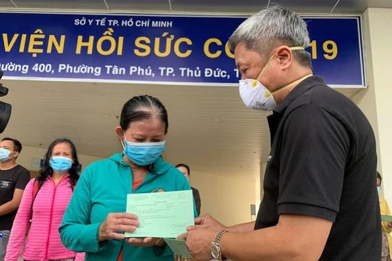 衛生部副部長阮長山本月二十六日在新冠肺炎加護醫院向 康復者交予出院證明書。