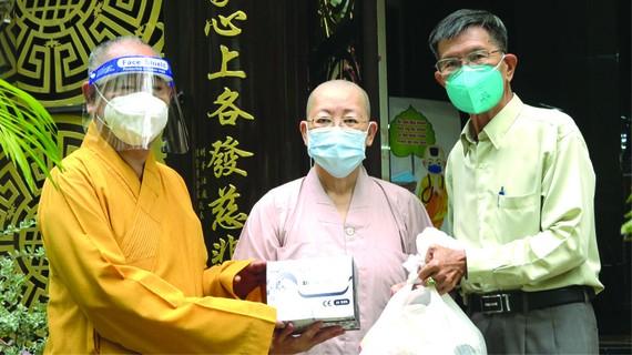 釋慧功和尚、陳健安居士向觀音精舍 監院釋振靜尼師贈送素食品及新冠病毒檢 測用具。