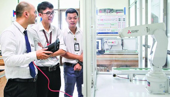 Students of the automation major in their practice lesson to control robots. (Photo: SGGP)