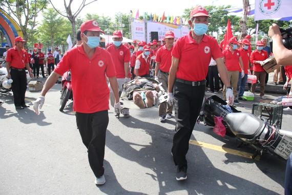 Các tình nguyện viên Chữ thập đỏ di chuyển người bị thương đến xe, điểm cấp cứu