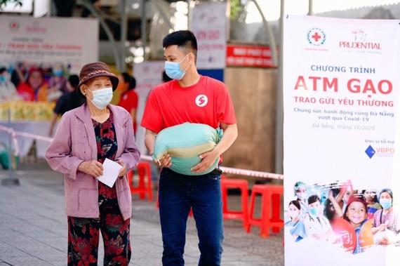 Một tình nguyện viện của Prudential Việt Nam đang giúp một người dân mang gạo