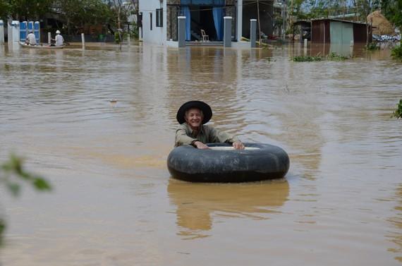 Một số người dân dùng phao bơi để vượt qua vùng nước lụt