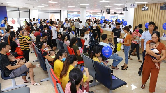 Người dân chờ đến lượt tiêm chủng cho trẻ sáng 11-7 tại Trung tâm VNVC Thanh Hóa