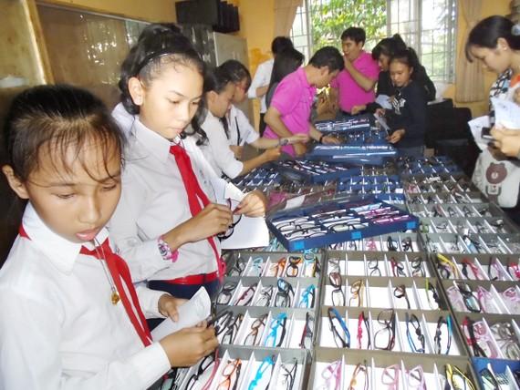 Các học sinh vùng sâu tỉnh Kiên Giang lựa kính do đoàn khám bệnh từ thiện của Hội Mắt kính TPHCM tặng
