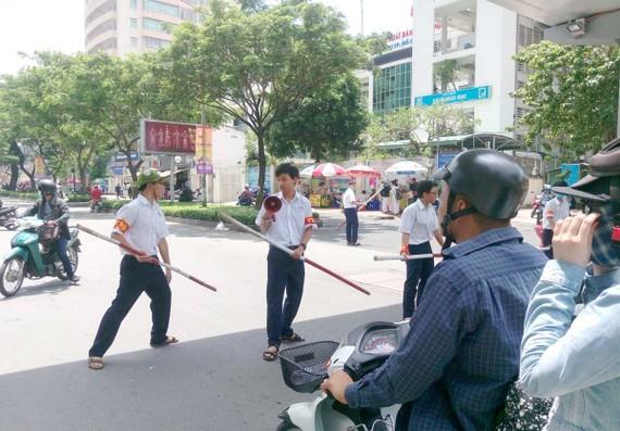 Đội trật tự học đường của Trường THPT chuyên Lê Hồng Phong (TPHCM) tham gia điều phối giao thông trước cổng trường giờ tan học. Ảnh: THU HƯỜNG